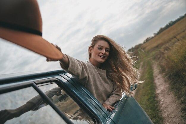 Po prostu zrelaksuj się i poczuj drogę. atrakcyjna młoda uśmiechnięta kobieta wychylająca się przez okno furgonetki i trzymająca kapelusz podczas jazdy samochodem
