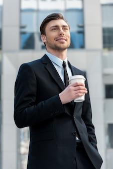 Po przerwie. portret młodego biznesmena pijącego poranną kawę na zewnątrz