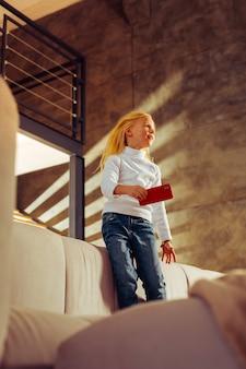 Po przerwie. słodkie dziecko stojące na łóżku, trzymające telefon swojej matki