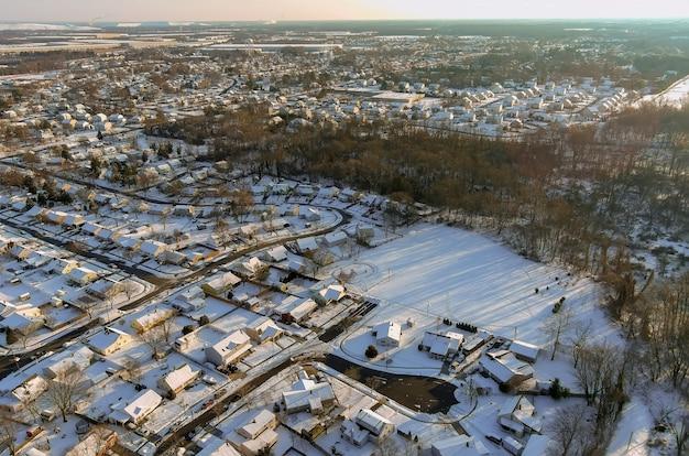 Po śniegu nad małym miasteczkiem mieszkalnym z dachami pokrytymi śniegiem domy w usa wsi zimowy widok z lotu ptaka