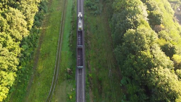 Po torach jedzie pociąg spalinowy z dwoma pustymi wagonami.