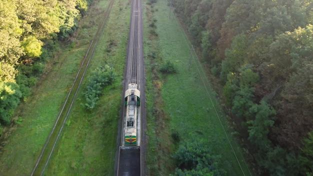 Po torach kolejowych przez las pędzi pociąg spalinowy. widok z lotu ptaka.