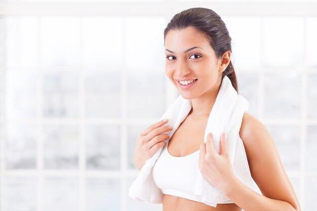 Po treningu. wesoła młoda indianka w sportowej odzieży trzyma ręcznik na ramionach i uśmiecha się do kamery