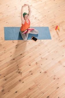 Po treningu. widok z góry kobiety noszącej ubrania sportowe, która odpoczywa po intensywnym treningu w domu