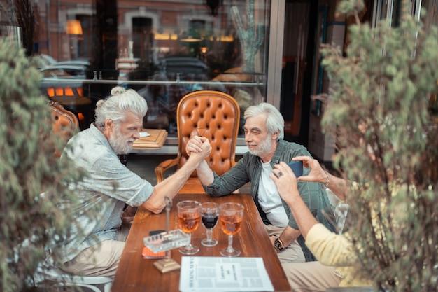 Po wypiciu alkoholu. emeryci siwy mężczyźni siłują się na rękę po wypiciu alkoholu poza pubem