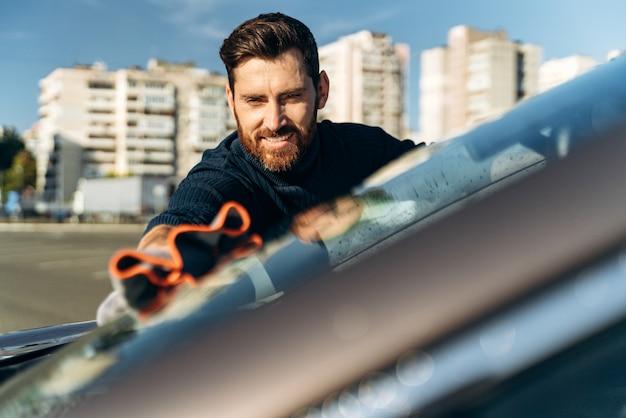 Po wypolerowaniu ręcznie przetrzyj powierzchnię lakieru błyszczącego samochodu. uśmiechnięty mężczyzna czyszczenie samochodu i suszenie pojazdu ściereczką z mikrofibry. koncepcja detalowania samochodu i myjni samochodowej