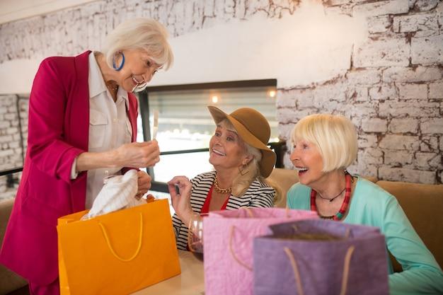 Po zakupach. wesołe starsze kobiety z torbami na zakupy wyglądające na szczęśliwe