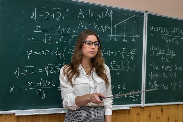 Po zapisaniu równania matematycznego młody nauczyciel wzywa ucznia do tablicy, aby mógł wszystko wyjaśnić
