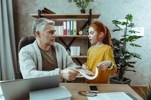 Pobaw się ze mną. urocza rudowłosa dziewczyna rozmawiająca z ojcem, prosząc o jego uwagę