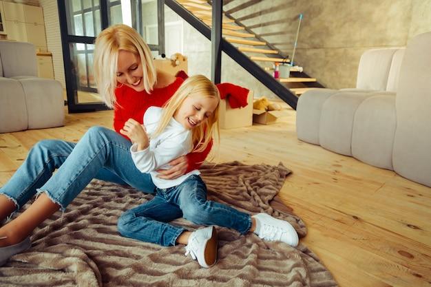 Pobaw się ze mną. zadowolona kobieta pochyla głowę, patrząc na swoją córkę her