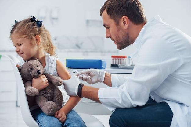 Pobieranie próbek krwi. mała dziewczynka jest w klinice z lekarzem.