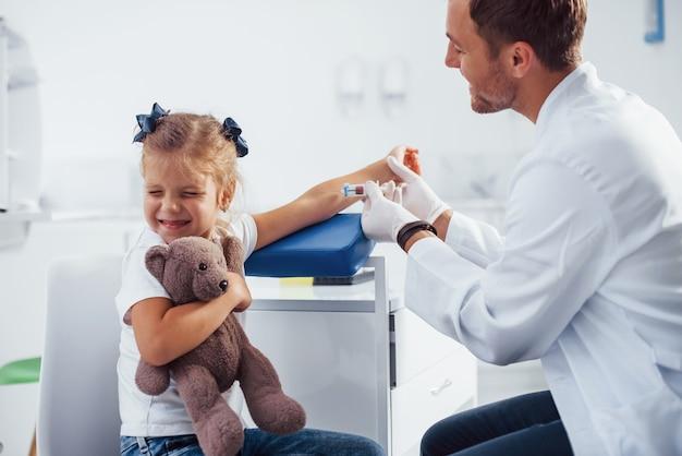 Pobieranie próbek krwi. mała dziewczynka z misiem jest w klinice z lekarzem.