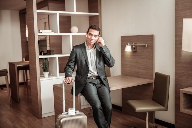 Pobyt w hotelu. młody i odnoszący sukcesy biznesmen afroamerykański przebywający w hotelu po podróży służbowej