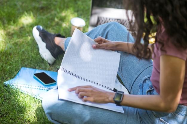 Pobyt w parku. ciemnoskóra kobieta siedząca na trawie i studiująca