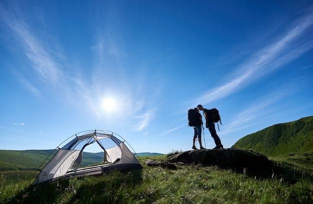 Pocałuj kochanków w górach w słońcu z niesamowitym krajobrazem zielonych wzgórz pod niebieskim niebem. połącz z plecakami i kijami trekkingowymi