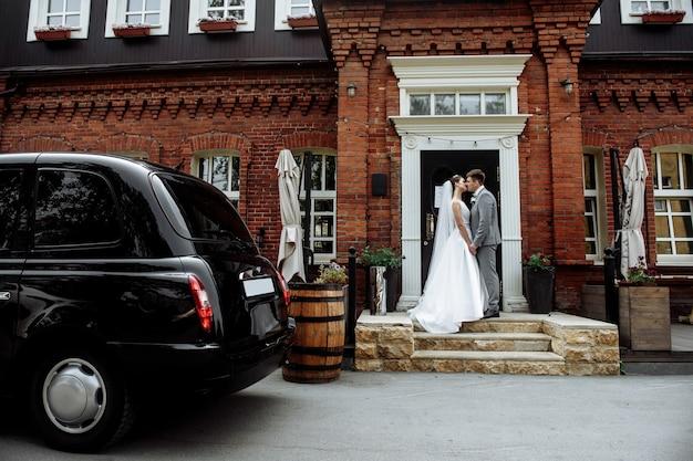 Pocałunek młodego pana młodego, panny młodej i panny młodej obok samochodu w sukniach ślubnych w anglii. piękni nowożeńcy