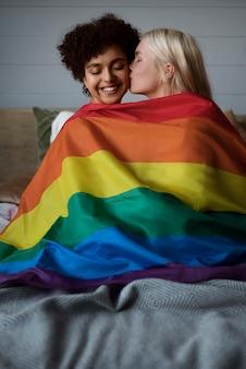 Pocałunek pary lesbijek z flagą lgbt
