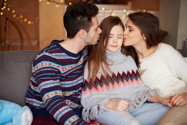 Pocałunek w policzek dziewczynki od rodziców