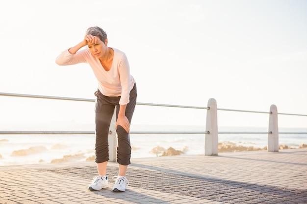 Pocenie sporty kobieta odpoczywa przy deptakiem