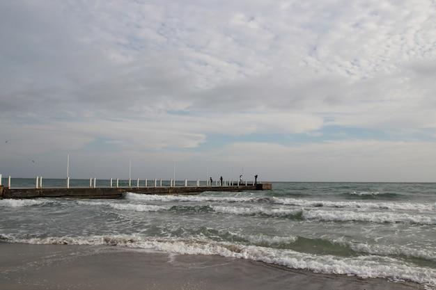 Pochmurna pogoda. złoty piasek, fale i piana. pochmurny dzień na piaszczystej plaży. panoramiczny widok pięknej, piaszczystej plaży. plaża i fale z ponurym niebem.