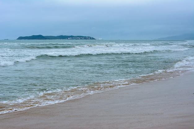 Pochmurny dzień, piasek opustoszała plaża u wybrzeży zatoki haitang na morzu południowochińskim. sanya, wyspa hainan, chiny. przyroda krajobraz.