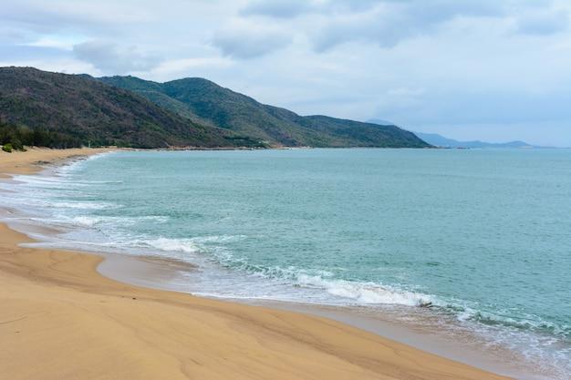 Pochmurny dzień, piaszczysta bezludna plaża wybrzeża w pobliżu posągu bogini nanshan na morzu południowochińskim. sanya, wyspa hainan, chiny. przyroda krajobraz.