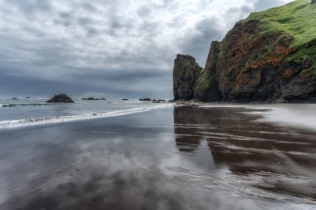 Pochmurny krajobraz odbity w mokrych piaskach plaży