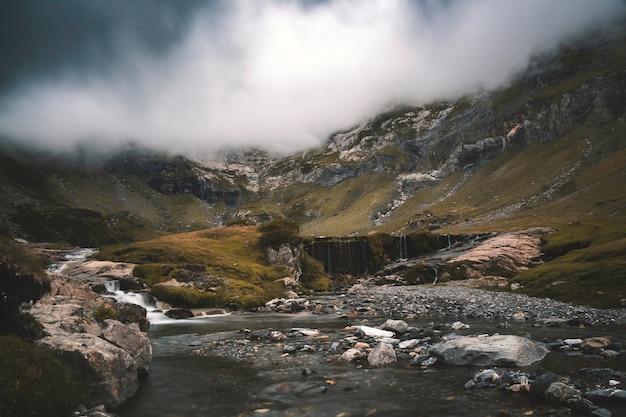 Pochmurny krajobraz z rzeką schodzącą w dół i prześladowaniem burzy.