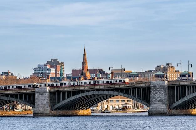 Pociąg biegnący przez most longfellow na rzece charles w godzinach wieczornych, panoramę centrum usa