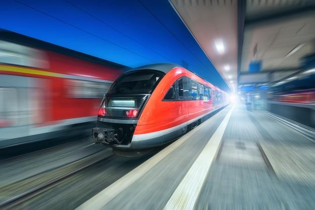 Pociąg dużych prędkości w ruchu na stacji kolejowej w nocy