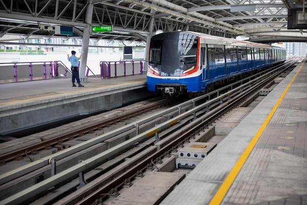 Pociąg elektryczny i bezpieczeństwo z powrotem trzymając rękę na stacji w tajlandii