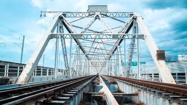 Pociąg estakada nad rzeką. most kolejowy z żelaza.