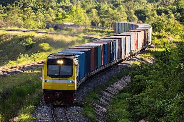 Pociąg kontenerowy przejeżdża przez zielone pola