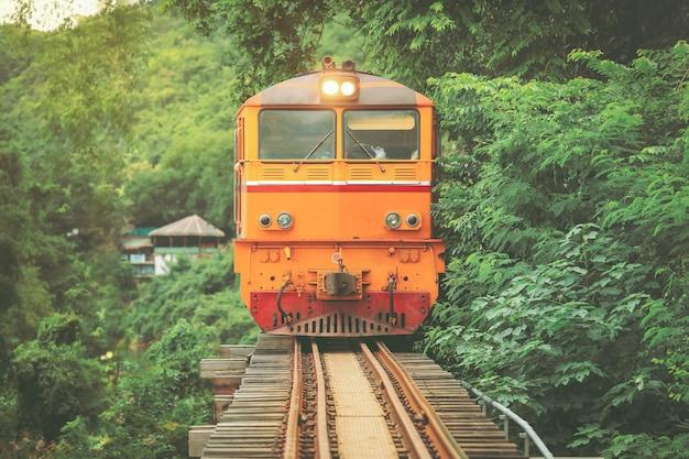 Pociąg na moscie nad rzecznym kwai w kanchanaburi, tajlandia. ten most słynie z historii w czasie drugiej wojny światowej.