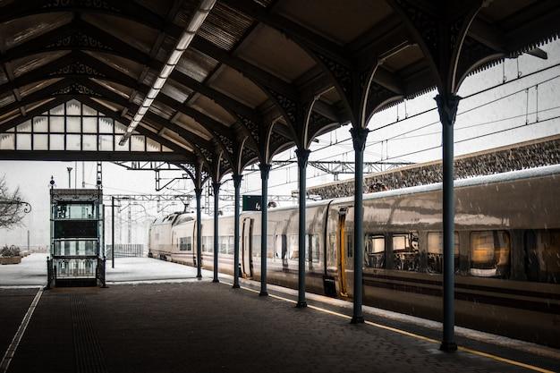 Pociąg na stacji kolejowej pokrytej zimą śniegiem