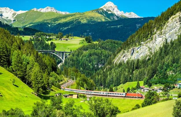 Pociąg pasażerski na kolei brenner w austriackich alpach
