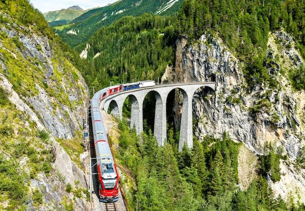 Pociąg pasażerski przejeżdżający przez wiadukt landwasser w alpach szwajcarskich