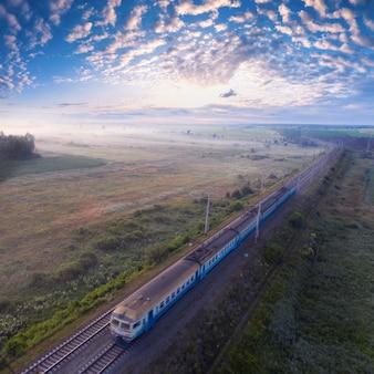 Pociąg towarowy jedzie przez mglisty las.