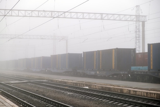 Pociąg towarowy poruszający się na peronie pociąg towarowy przejeżdżający przez stację. wagony jeżdżą na kolei stalowej. koncepcja transportu przemysłu ciężkiego.