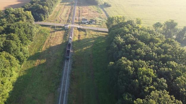 Pociąg towarowy przejeżdża przez autostradę na skrzyżowaniu.