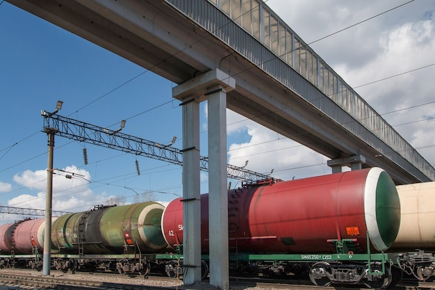 Pociąg towarowy ze zbiornikami stoi na szynach pod wiaduktem na stacji dworca miejskiego