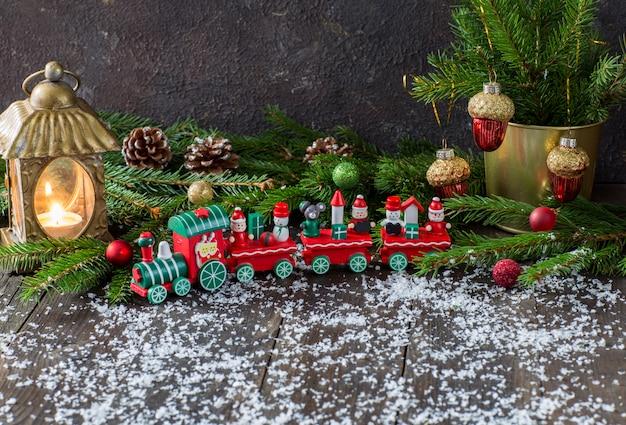 Pociąg zabawka, latarnia ze świecą, gałęzie sosny i świąteczny wystrój