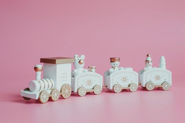 Pociąg zabawki. świąteczne dekoracje na różowym tle