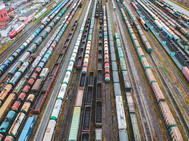 Pociągi towarowe. widok z lotu ptaka kolorowi pociągi towarowi na stacji kolejowej. wagony z towarami na kolei. przemysł ciężki. przemysłowa konceptualna scena z pociągami. widok z latającego drona.