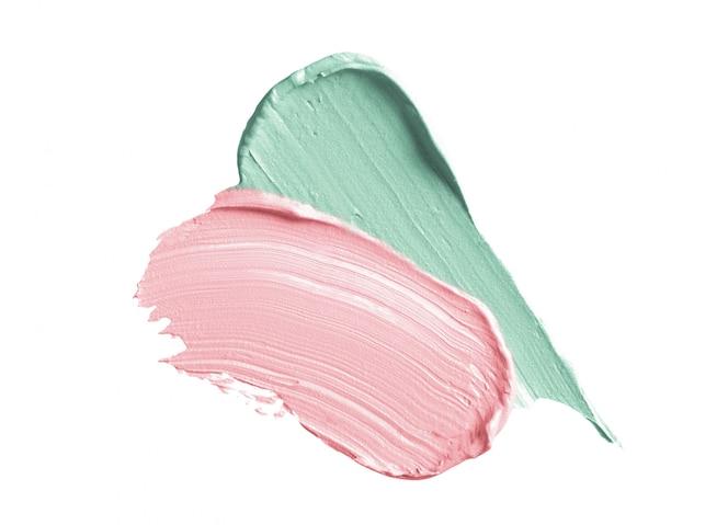 Pociągnięcia korektora w kolorze zielonym i różowym na białym tle