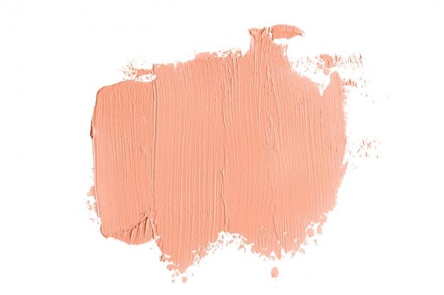 Pociągnięcia pędzlem korektora koloru brzoskwini na białym tle
