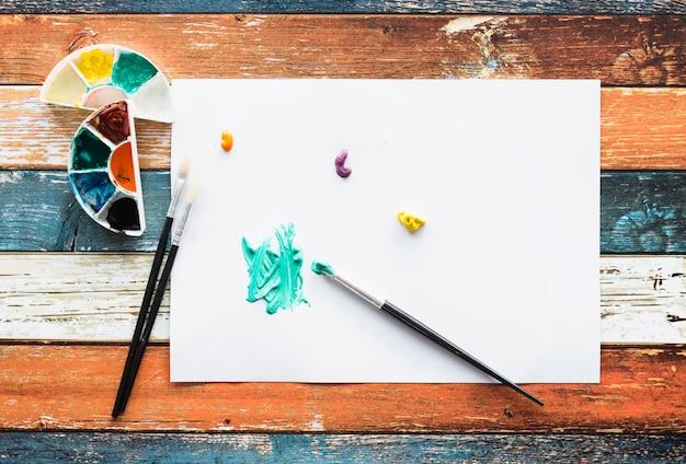 Pociągnięcie pędzlem i plamy farby na białej stronie na drewniane biurko