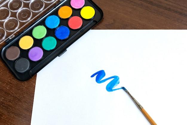 Pociągnięcie pędzlem niebieskiej farby akrylowej i pędzel obok niego. odizolowywa na białym tle