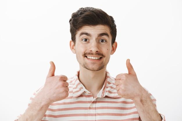 Pociesz się człowieku, wszystko świetnie. portret pozytywnego, przyjaznego kaukaskiego faceta z wąsami, podnoszącego kciuki i szeroko uśmiechającego się, aprobującego nową koncepcję lub pomysł przyjaciela, radosnego i zadowolonego