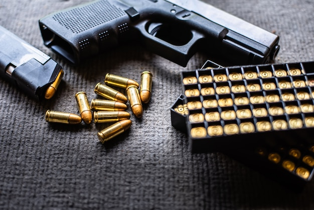 Pociski i pistolet na biurku z czarnego aksamitu